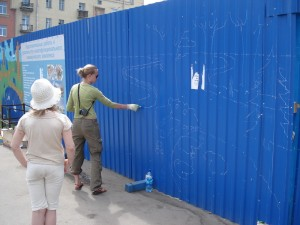 Yulia Avgustinovich drawing the outlines for the fence murals surrounding metro construction zone